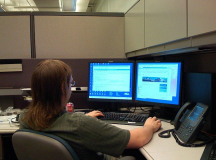 An office worker with a dual-monitor display