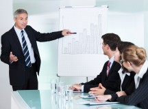 Business man showing to charts at a meeting-Shutterstock